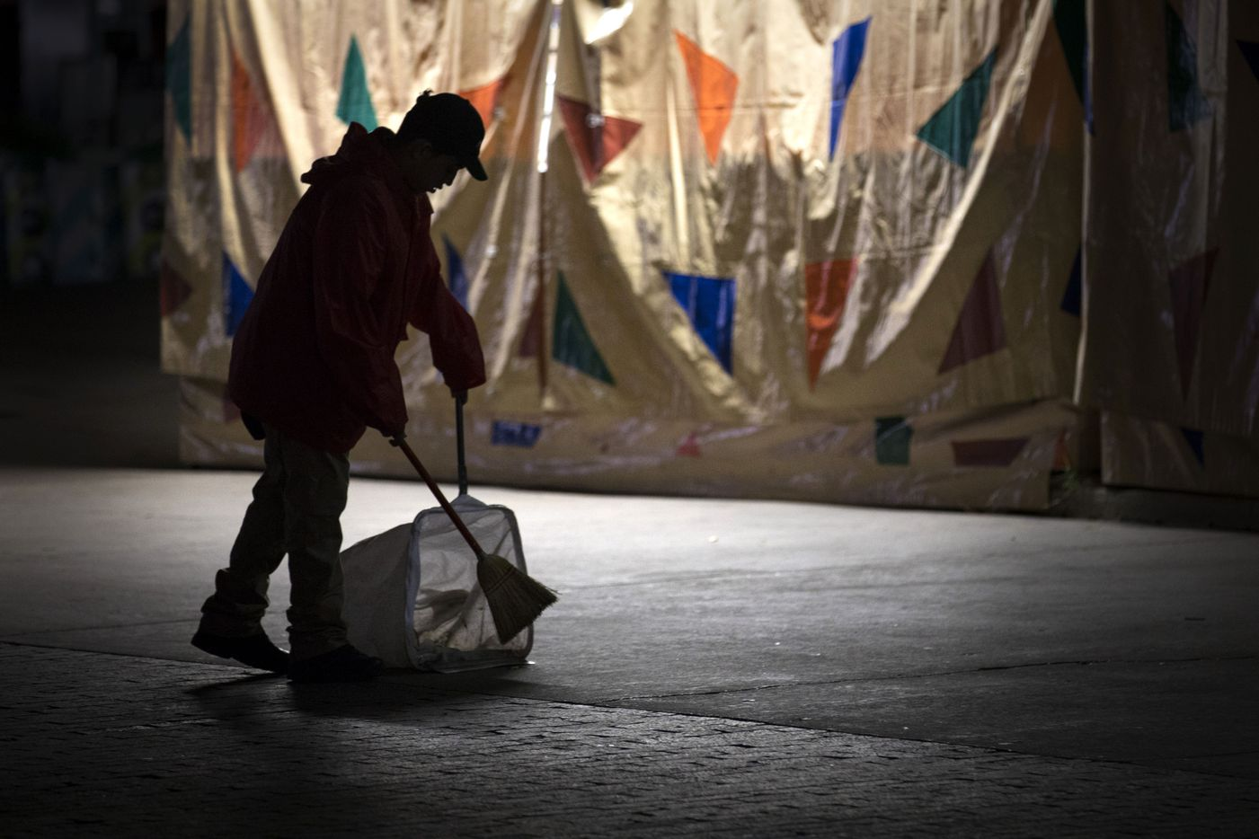 A worker sweeps up along Grand Avenue at the State Fair of Texas in the early morning hours.