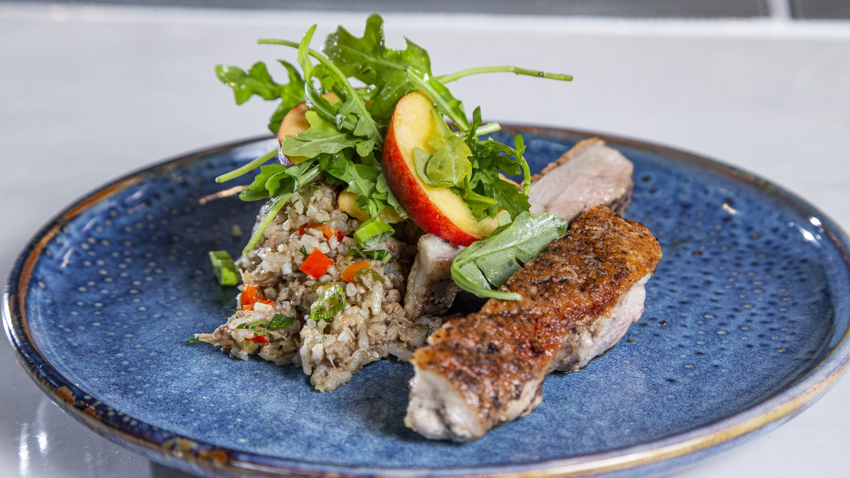 Roots Southern Kitchen's menu includes Peking duck dirty rice with peach salad. Roots is former 'Top Chef' contestant Tiffany Derry's new restaurant in Farmers Branch.