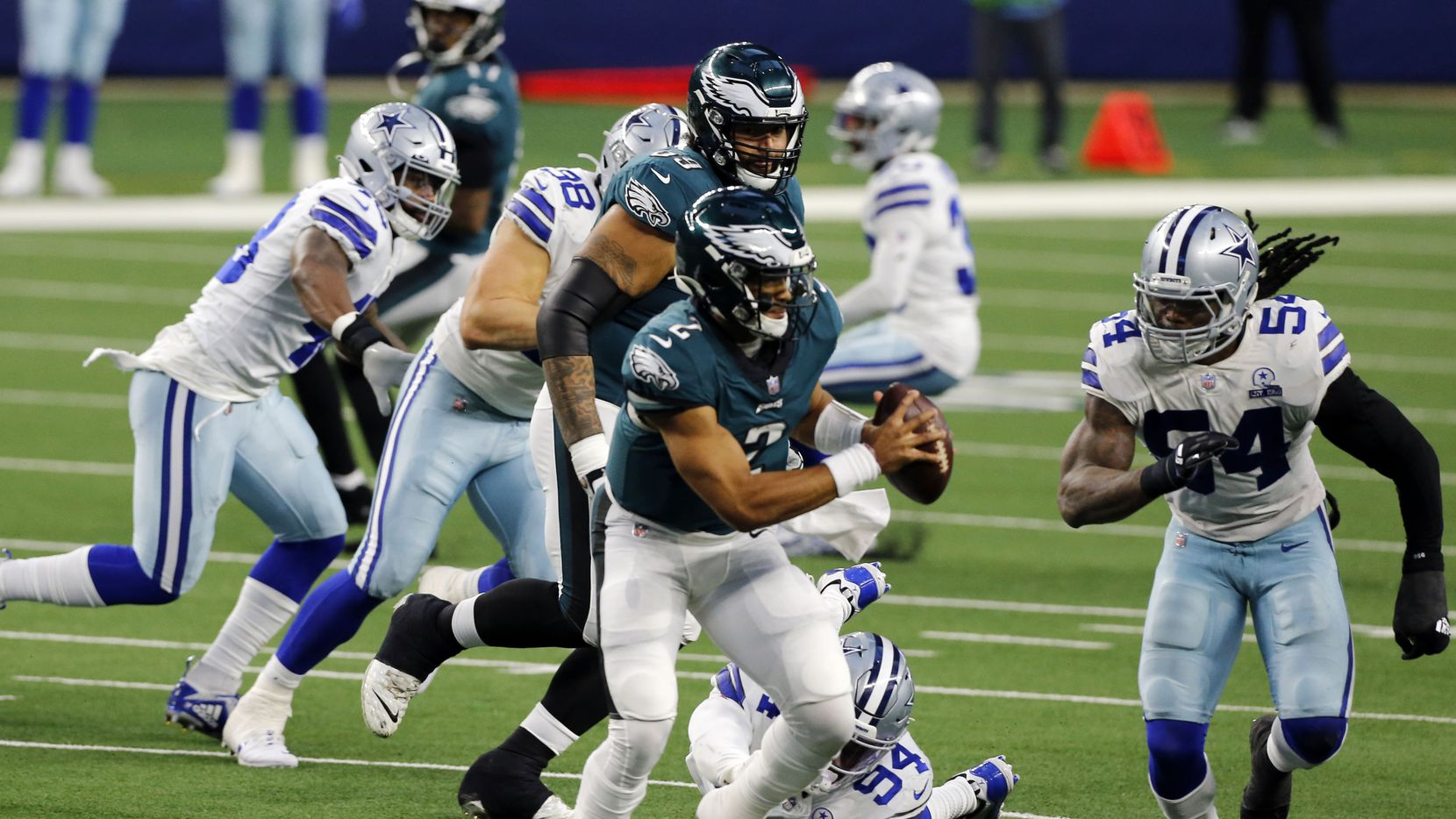 Philadelphia Eagles quarterback Jalen Hurts (2) is boxed in by Dallas Cowboys defensive end Randy Gregory (94) and middle linebacker Jaylon Smith (54) during the second half of a NFL football playoff game between against the Philadelphia Eagles and the Dallas Cowboys at AT&T Stadium in Arlington on Sunday, December 27, 2020. The Cowboys won 37-17.