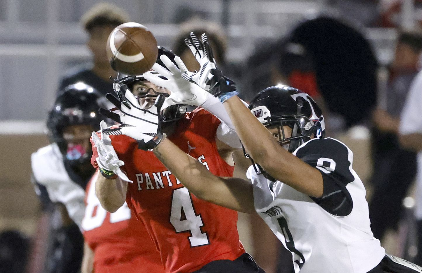 Euless Trinity defender Tovo Asaeli, right, breaks up a pass intended for Colleyville Heritage receiver Hogan Wasson (4), left,  during the first half of a high school football game in Grapevine, Texas on Friday, Sept. 10, 2021. (Michael Ainsworth/Special Contributor)