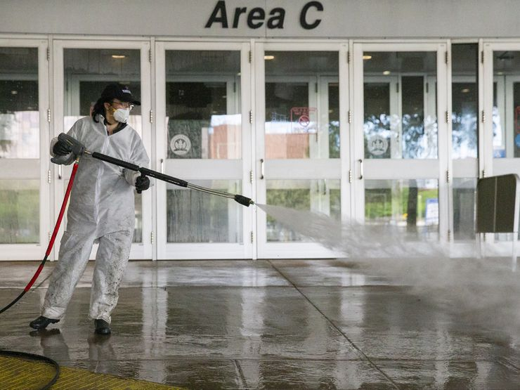 A worker power washes an entrance to the Kay Bailey Hutchison Convention Center in downtown Dallas Sunday. On Friday, Gov. Greg Abbott announced that Texas has 19,695 available hospital beds, up from 8,155 on March 18.