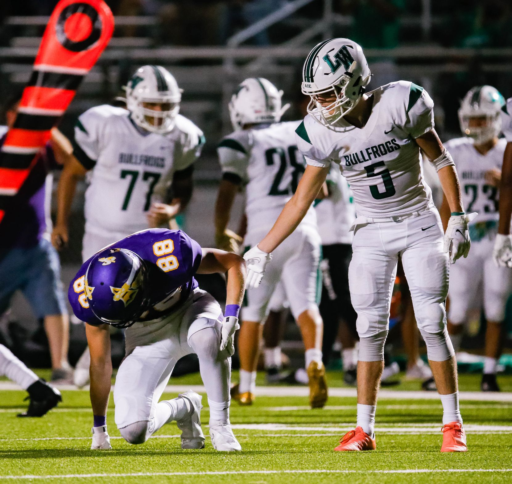 Lake Worth High School's Mark Fulkerson (5) offers Sanger High School's Dewey Terreault (88) a hand after he missed a pass during the second half of a game on Sept. 4, 2020 in Sanger. Sanger won 49-35. (Juan Figueroa/ The Dallas Morning News)