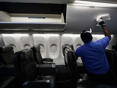 A cabin cleaner with ABM Aviation wipes down the overhead bins of an American Airlines aircraft with disinfectant at DFW International Airport Terminal A in June. U.S. airlines say they've been consulting with disease specialists while rushing to respond to an outbreak that's prompted billions of dollars in losses.