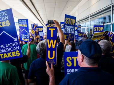 American Airlines employees protest the lack of a new contract for baggage carriers, mechanics and other staff on Wednesday, July 26, 2017 outside Terminal D at Dallas/Fort Worth International Airport.