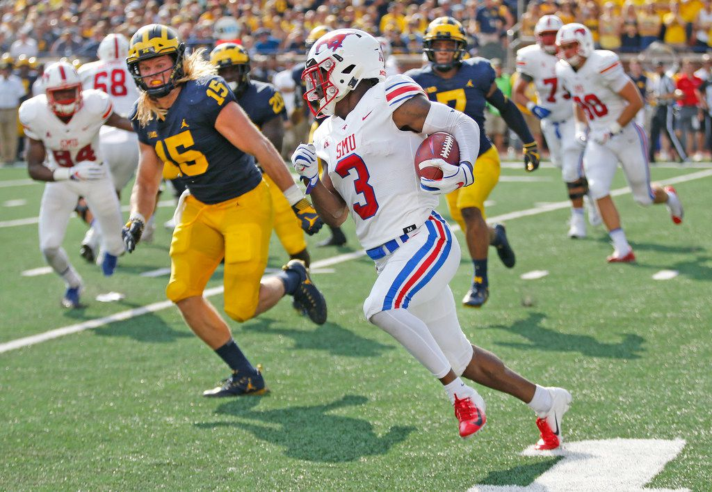 Southern Methodist Mustangs wide receiver James Proche (3) motors for yardage as Michigan Wolverines defensive lineman Chase Winovich (15) pursues during the SMU Mustangs vs. the Michigan Wolverines NCAA football game at Michigan Stadium in Ann Arbor, Michigan on Saturday, September 15, 2018. (Louis DeLuca/The Dallas Morning News)