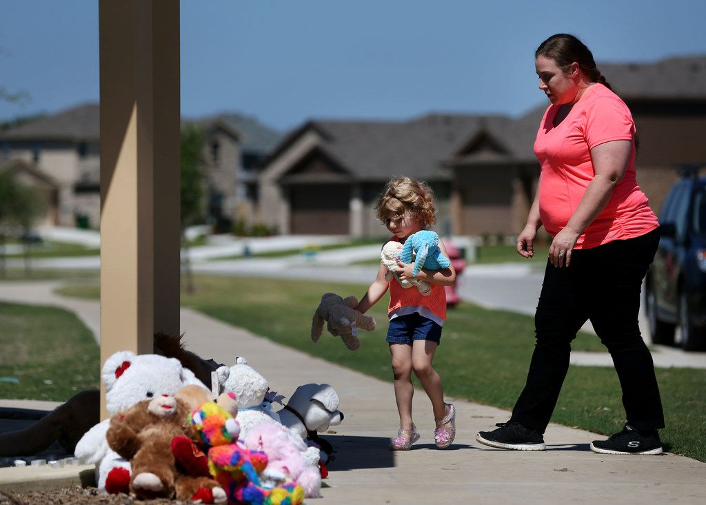 Judith McDuffie, 4, carries stuffed animals to place at a memorial with her mother Amanda McDuffie for the family that was killed May 16, 2018, in the Remington Park neighborhood of Ponder. Police say a man shot his ex-wife, three children and her boyfriend at a home Wednesday morning before turning the gun on himself. The ex-wife survived the shooting.