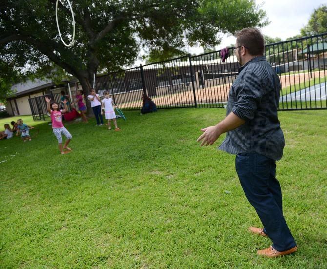 Pastor Leonid Regheta throws a hula hoop to Anya Malamis, 7, during summer camp at River of Life, an evangelical Christian church that caters to Russian-speaking immigrants, which operates out of Hunters Glen Baptist Church in Plano.