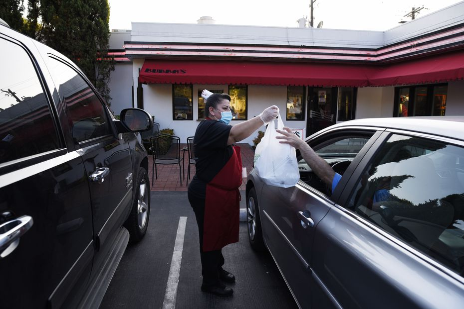 Claudia Beltran, center, hands a food order to a customer at the curbside parking outside of Bubba's Cooks Country in Dallas.