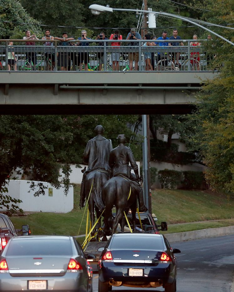 People take pictures of a truck carrying the Robert E. Lee statue from Katy Trail at Robert E. Lee Park in Dallas, Thursday, Sept. 14, 2017.
