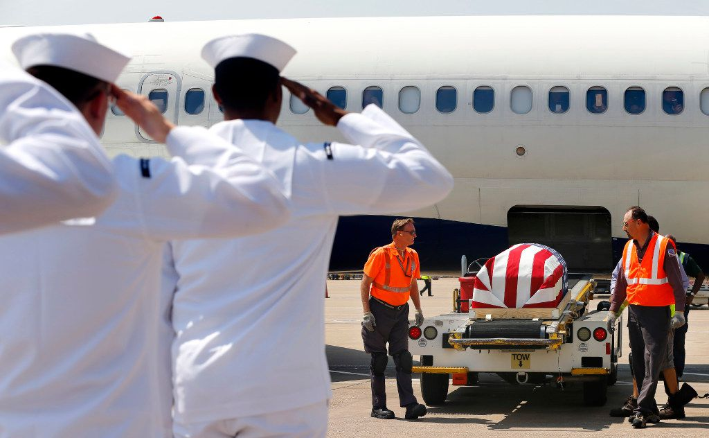 A Navy honor guard salutes as they remains of Seaman 1st Class George A. Coke Jr., of Arlington, are unloaded from a commercial flight at Dallas-Fort Worth International Airport, Friday, June 23, 2017, Grapevine, Texas. Coke, who perished aboard the USS Oklahoma after it sank at Pearl Harbor, was identified through recent DNA testing. A service for Coke will be held at First United Methodist Church in central Arlington Saturday before being buried at Parkdale Cemetery.