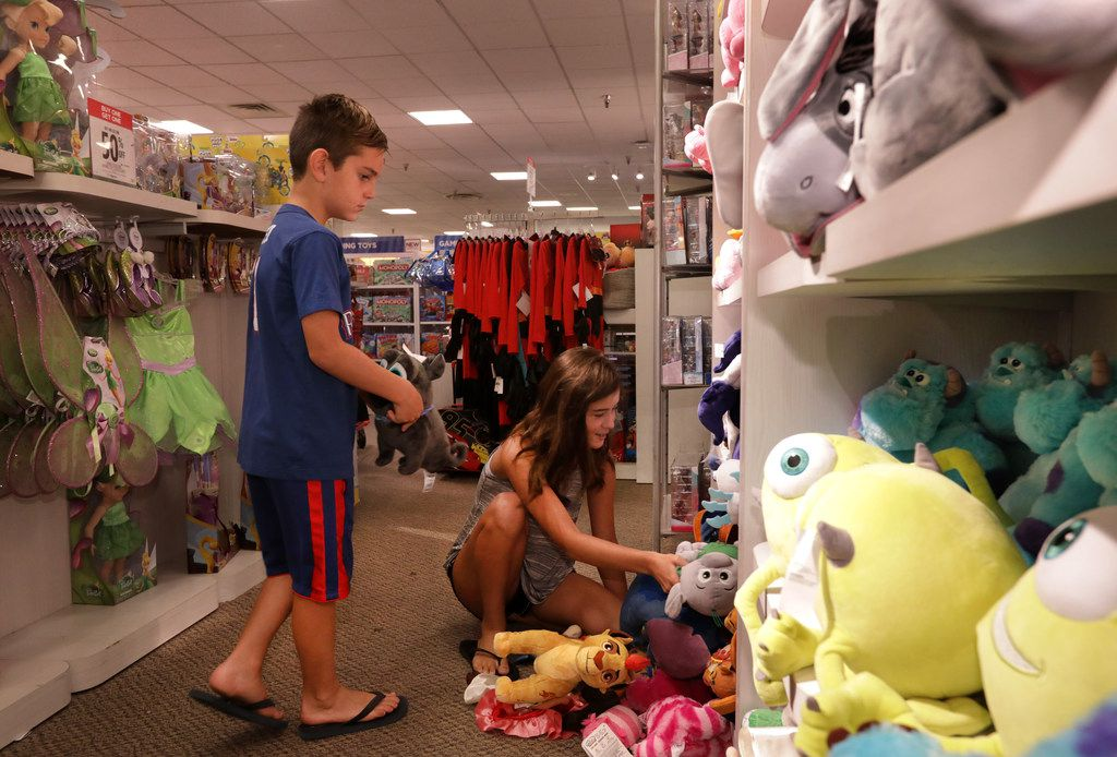 Mason Watson, 7, and 12-year-old Avery Watson check out the new toys at the Collin Creek Mall J.C. Penney in Plano.