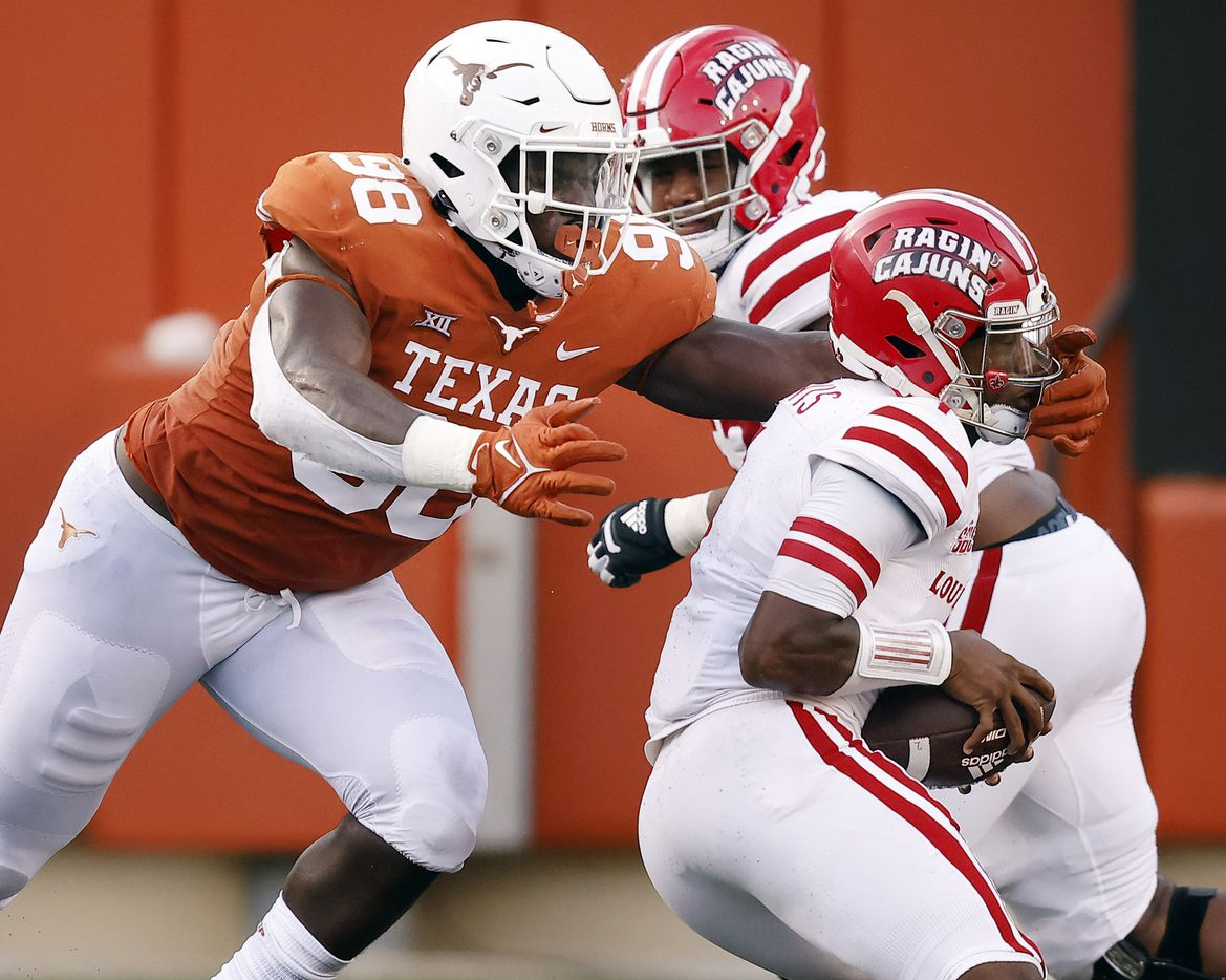 Texas Longhorns defensive lineman Moro Ojomo (98) reaches for Louisiana-Lafayette Ragin Cajuns quarterback Levi Lewis (1) for an attempted sack during the fourth quarter at DKR-Texas Memorial Stadium in Austin, Saturday, September 4, 2021. Lewis slipped out but was sacked by another player. (Tom Fox/The Dallas Morning News)