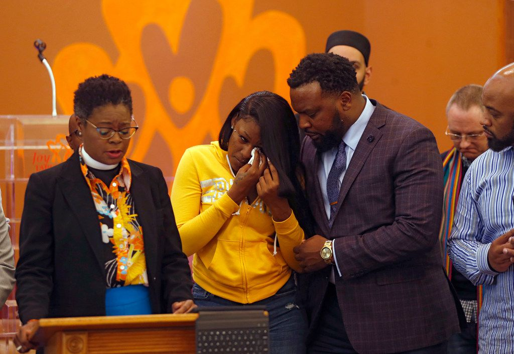 L'Daijohnique Lee (center) wipes away tears as she is consoled by her attorney, Lee Merritt (right) as Rev. Phea Kennedy (left), pastor of New Jerusalem AME Church of Dallas, speaks during a press conference denouncing violence against women at the Joy Empowerment Center in Dallas on Tuesday, March 26, 2019.