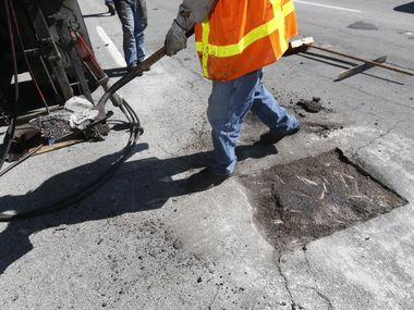 Dallas Street Services employees fix a pothole on Harry Hines Boulevard in Dallas.
