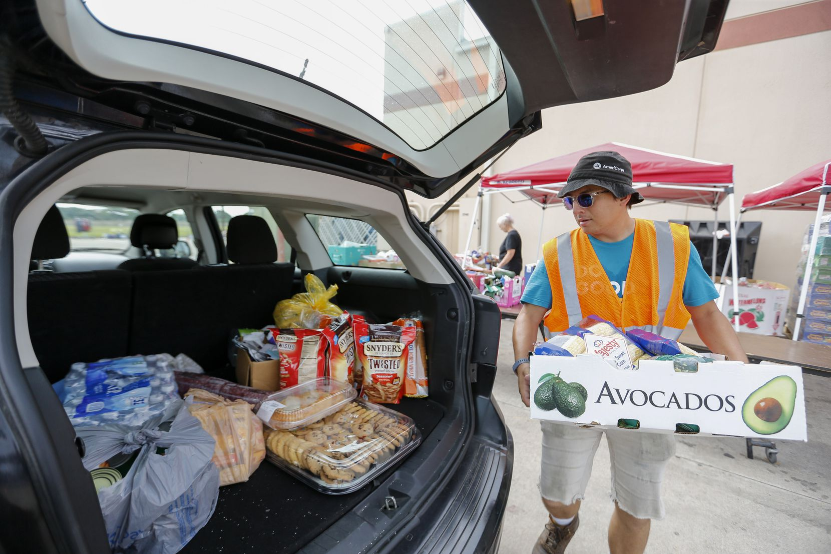 Gallarza loads food into a family's vehicle during Sharing Life's drive-thru pantry event.