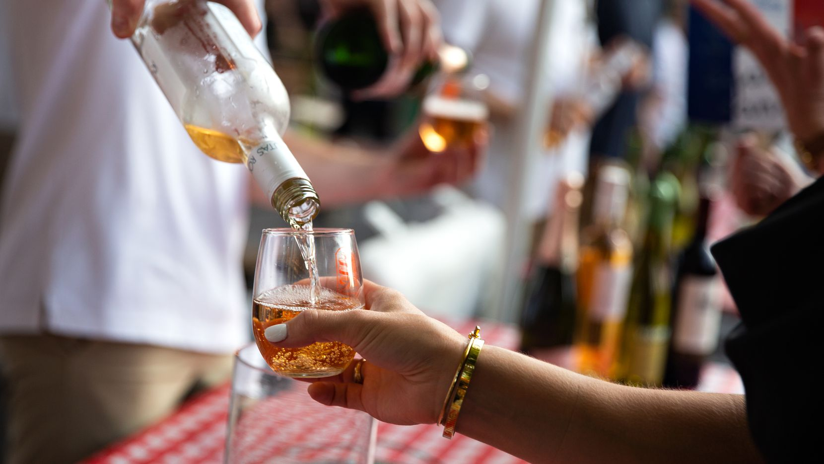 Festival goers are poured varieties of wine during an outdoor festival.