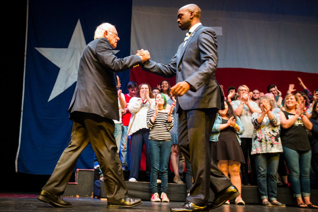 Bernie Sanders shakes hands with DNC vice chair Michael Blake as he takes the stage for a rally at the Verizon Theater.
