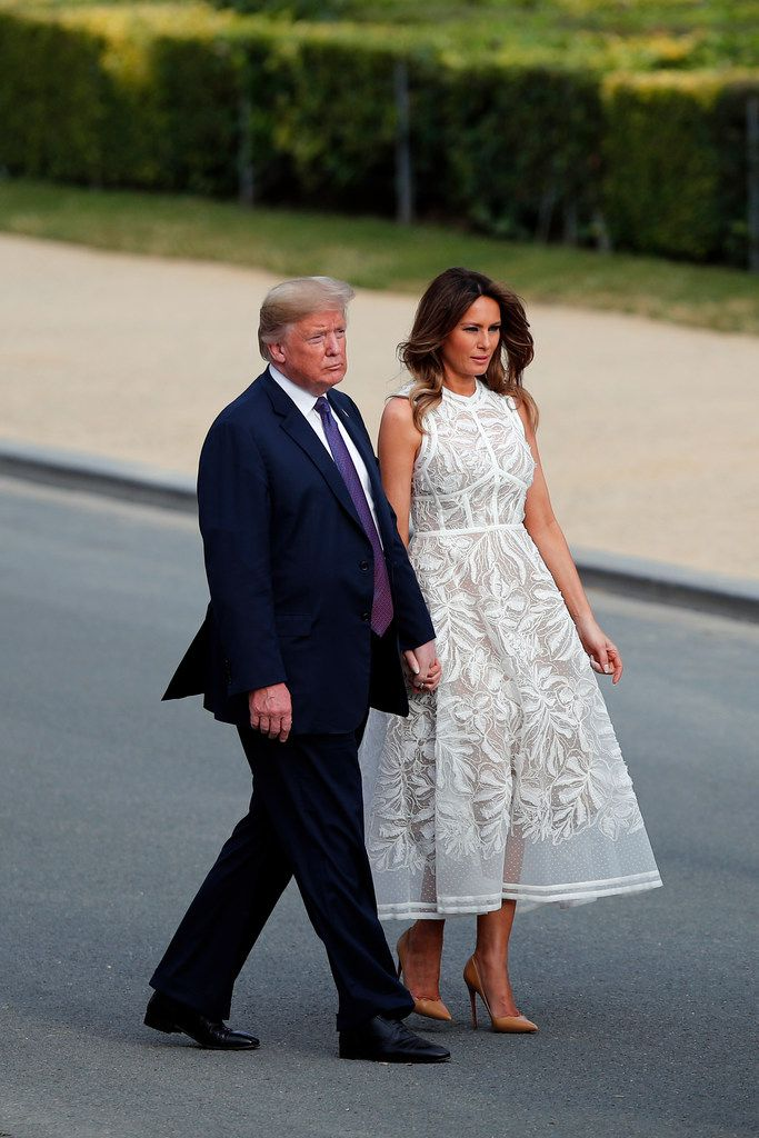 President Donald Trump and U.S. first lady Melania Trump walk after a group photo of NATO heads of state and government at Park Cinquantenaire in Brussels.
