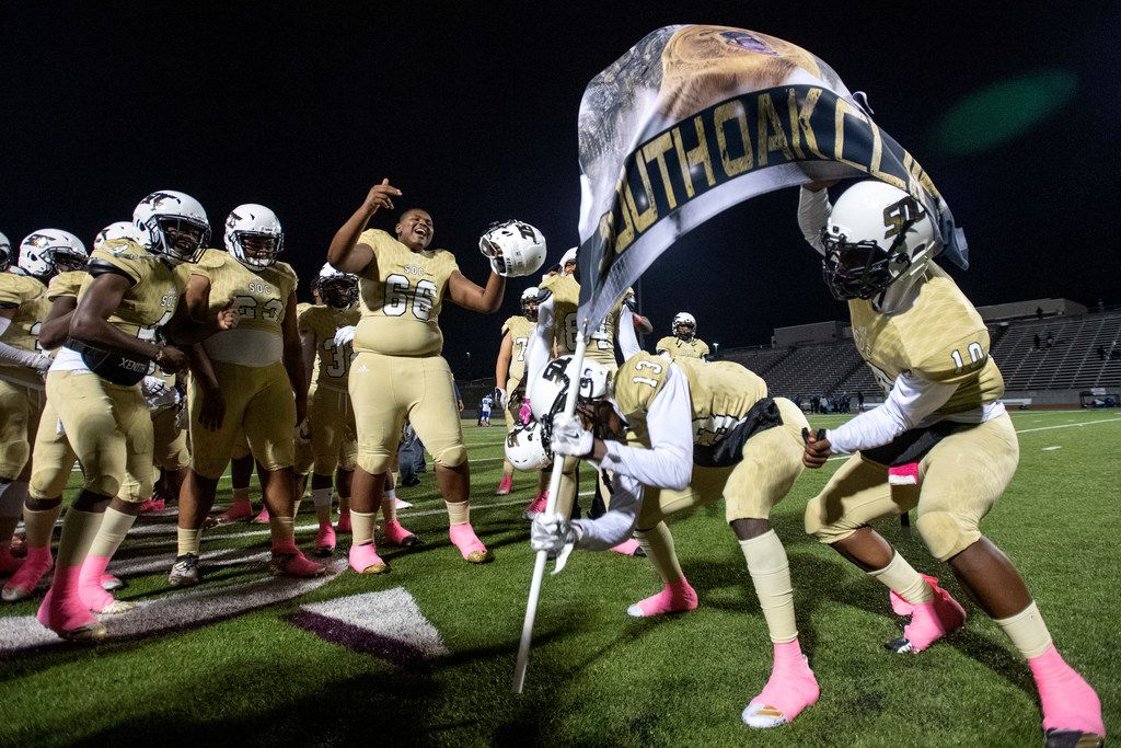 South Oak Cliff players cheers as junior wide receiver Justyn Harrison (13) and junior quarterback Mikeviun Titus (10) plant the school's flag after defeating Seagoville 41-8 in a high school football game on Friday, October 25, 2019 at Kincaide Stadium in Dallas.