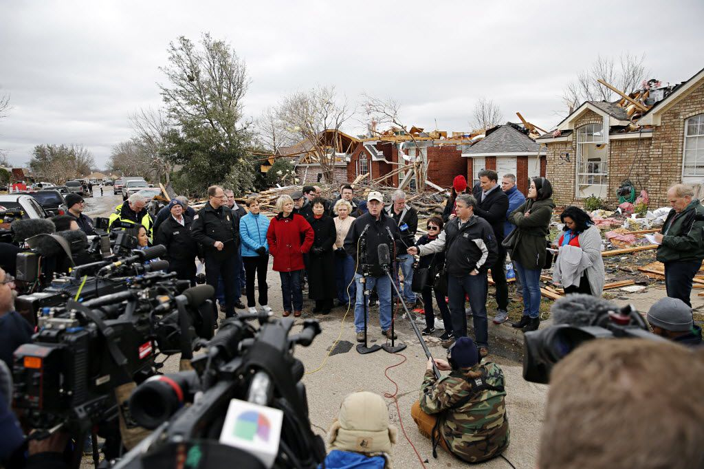 Garland Mayor Douglas Athas (center) addressed the media in a storm-damaged neighborhood Dec. 28, 2015 in Garland. Violent storms ripped through the North Texas area two days earlier, spawning tornados that killed 13 people, nine in Garland.