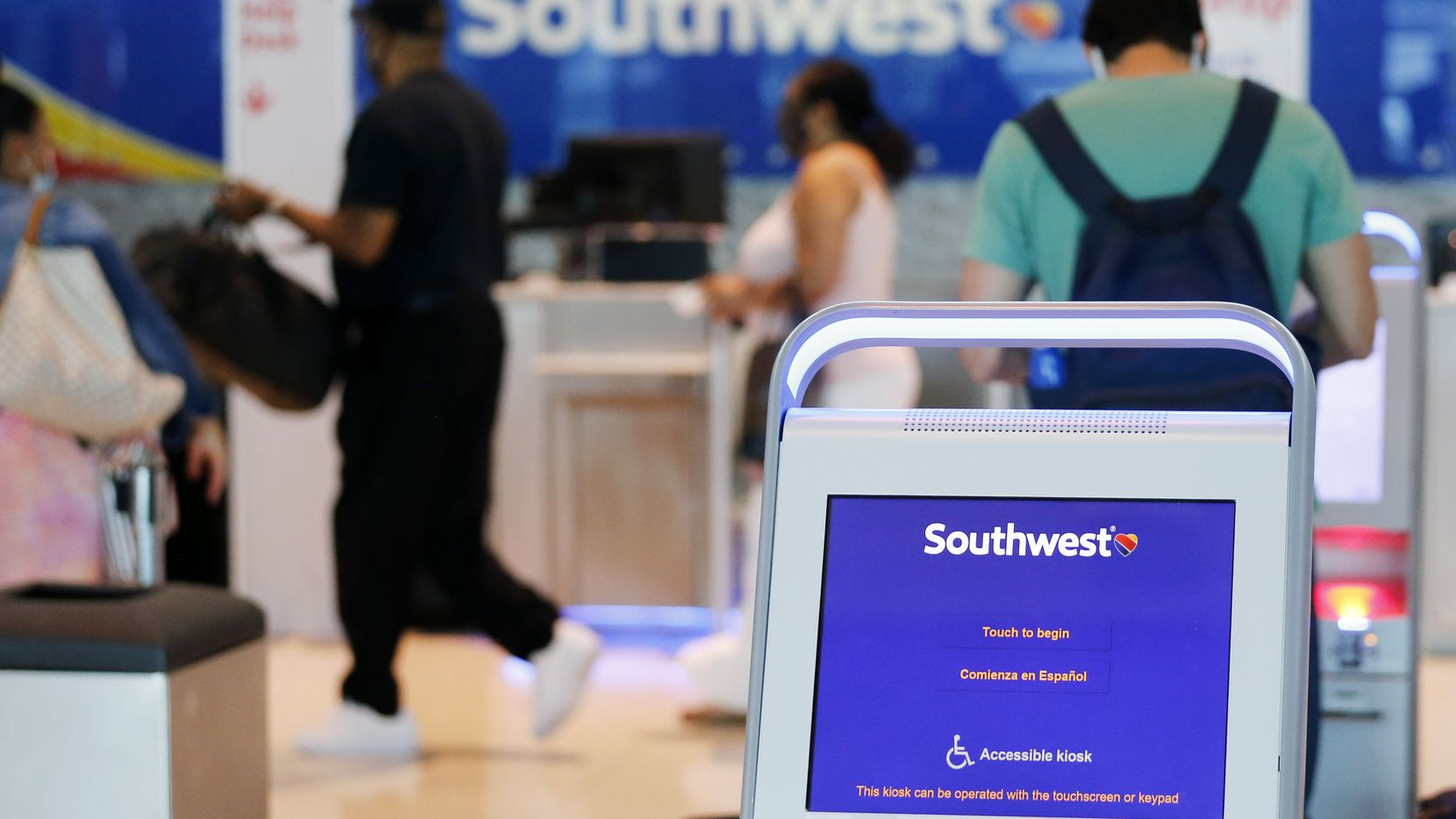 Southwest Airlines passengers prepare to check their baggage at Dallas Love Field Airport in Dallas, on Monday, July 20, 2020. (Vernon Bryant/The Dallas Morning News)
