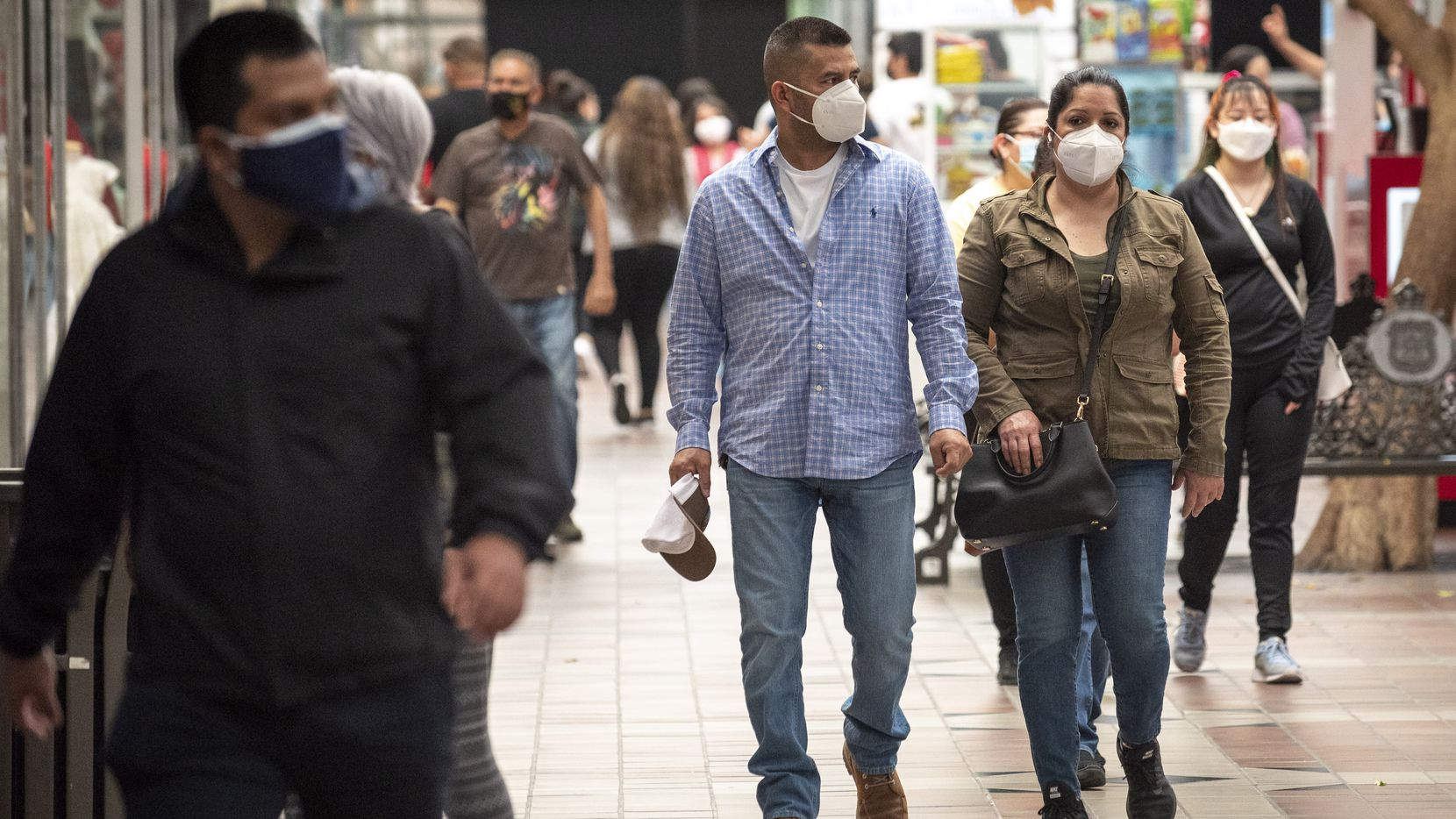 A couple wears face coverings while shopping at La Gran Plaza in Fort Worth, on March 6, 2021. Tarrant County Judge Glen Whitley said this week he will not issue a mask requirement.