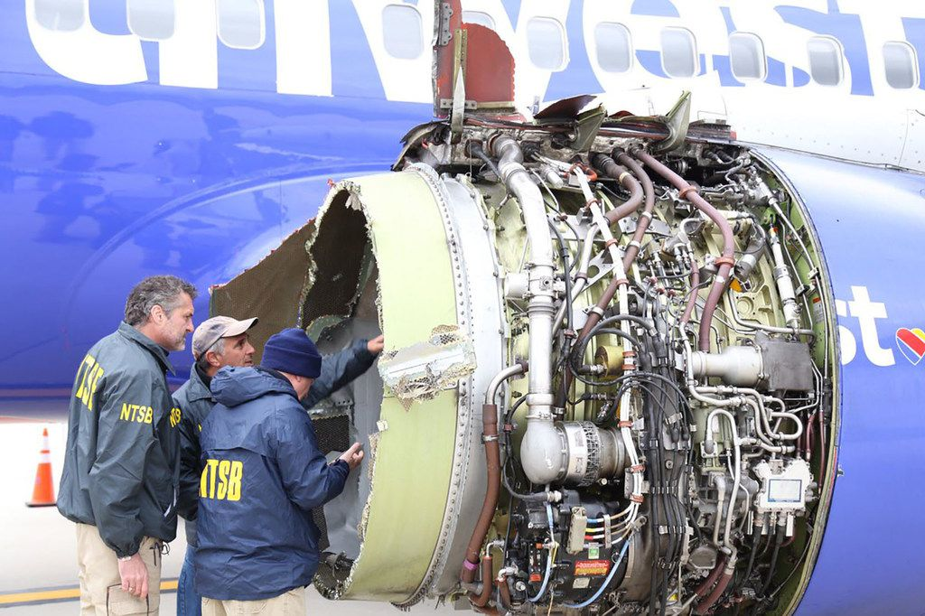 This photo obtained April 18, 2018 courtesy of the National Transportation Safety Board shows NTSB investigators on scene examining damage to the engine of the Southwest Airlines plane on April 17, 2018. Catastrophic engine failure on a Southwest Airlines flight from New York to Dallas killed a mother-of-two and forced an emergency landing April 17, 2018, the first fatal incident in US commercial aviation for nearly a decade.The Boeing 737-700 took off without incident but minutes into the flight, passengers heard an explosion in the left engine, which sent shrapnel flying through the window, shattering the glass and leading oxygen masks to drop, witnesses said.