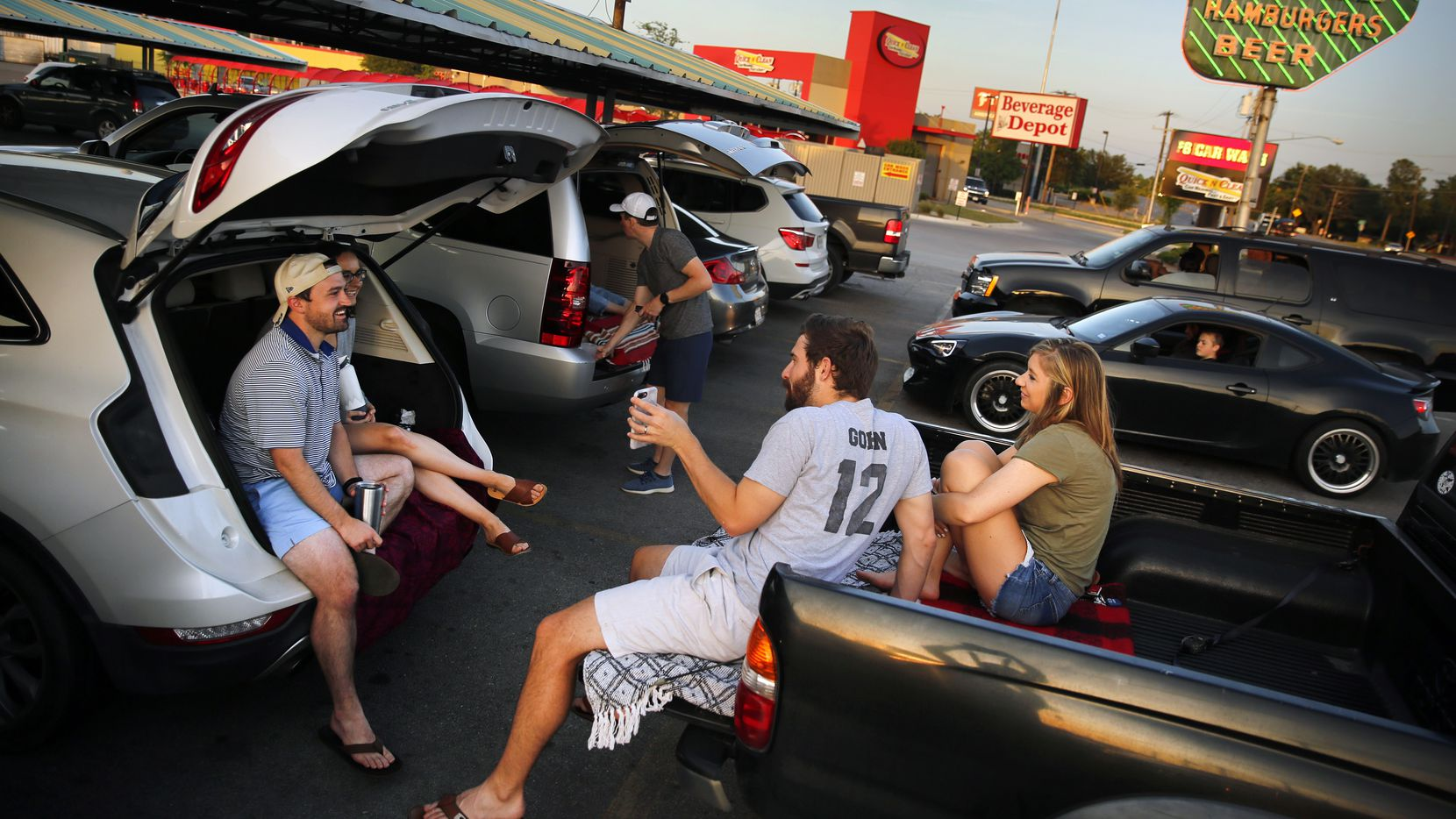 Japhen Lott and wife Miranda (left) tailgated with friends Jon Gohn and wife Lauren at Keller's Drive-In on Northwest Highway in Dallas on May 14, 2020. Researchers at UTHealth hope Texans will use a mobile app to help track symptoms as the state's economy reopens.