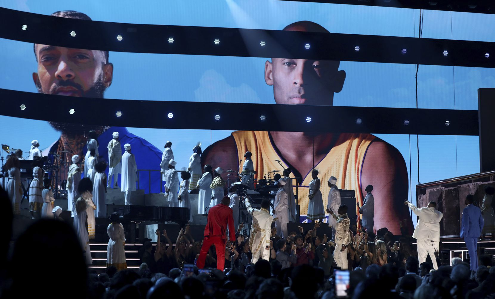 YG, from left, John Legend, Kirk Franklin, DJ Khaled and Meek Mill point to a screen showing Nipsey Hussle and Kobe Bryant during a tribute at the 62nd annual Grammy Awards on Sunday, Jan. 26, 2020, in Los Angeles.