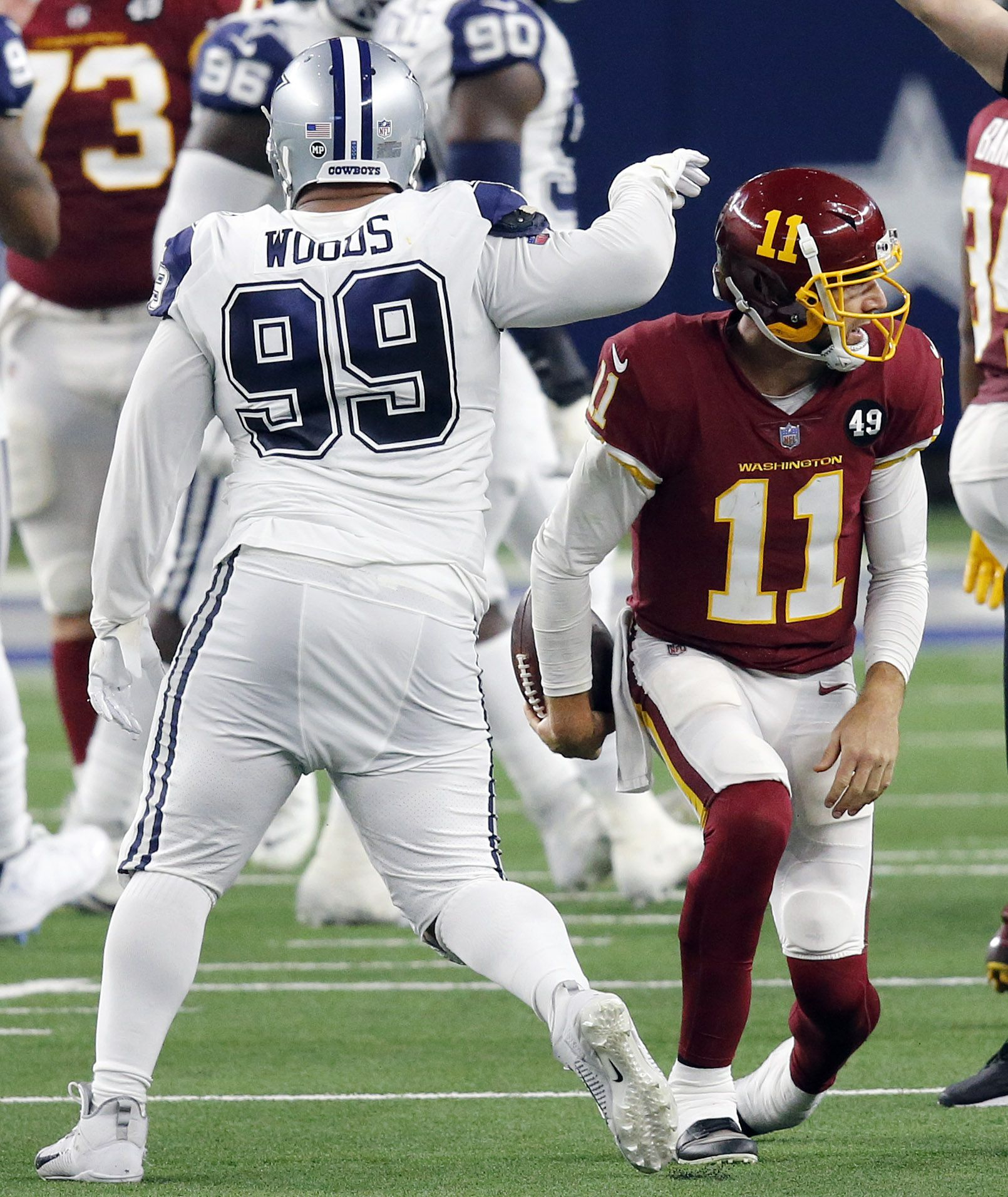 Dallas Cowboys defensive tackle Antwaun Woods (99) slaps Washington Football Team quarterback Alex Smith (11) on the head after forcing a sack in the third quarter at AT&T Stadium in Arlington, Thursday, November 26, 2020. (Tom Fox/The Dallas Morning News)