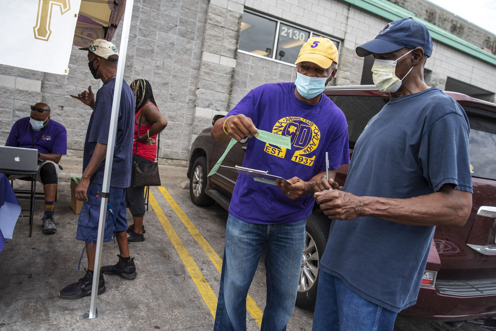 Nate Favaroth (center), a member of Omega Psi Phi fraternity, speaks to Ben Kennedy, 60, as he updates his voter registration information during a voter registration drive outside of the Cash Saver grocery store in South Dallas on Sept. 5, 2020. The fraternity, part of the National Pan-Hellenic Council, conducted the registration drive.