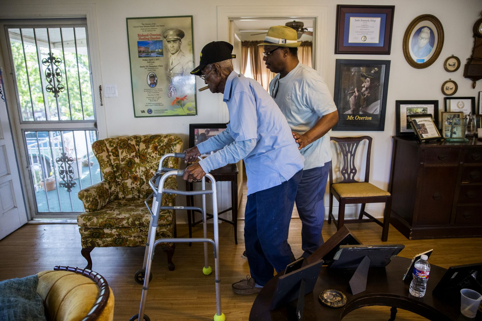 Richard Overton is escorted by family friend Martin Wilford through his living room to the front porch at 10:19 a.m. He spends much of his day there, smoking cigars, snooping on the neighbors, waving at honking cars and greeting visitors.