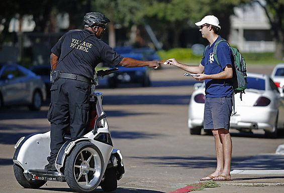 A security guard checks identification at The Village apartment complex in East Dallas