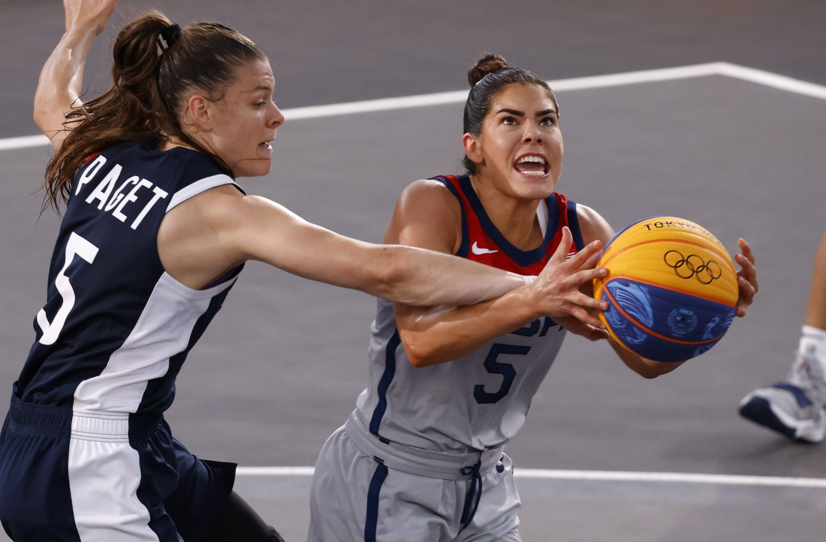 USA Kelsey Plum (5) is fouled as she attempts a shot in front of France's Marie-Eve Paget (5) in a 3x3 women's basketball game during the postponed 2020 Tokyo Olympics at Aomi Urban Sports Park on Saturday, July 24, 2021, in Tokyo, Japan. USA defeated France 17-10 in the game. (Vernon Bryant/The Dallas Morning News)