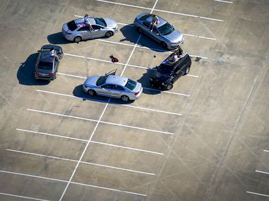 Young people gather in the parking lot of McKinney High School on Tuesday, March 24, 2020. After Dallas County's shelter-in-place order went into effect at midnight the night before, Collin County Judge announced a similar stay at home order effective immediately on Tuesday.