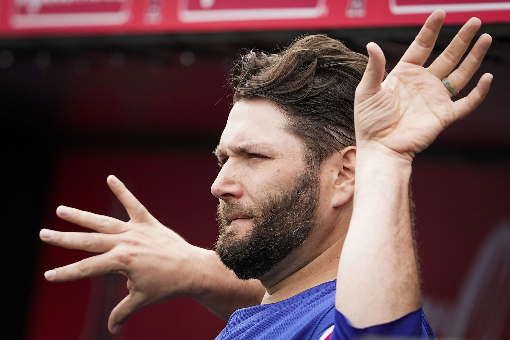 Texas Rangers pitcher Lance Lynn stretches in the dugout before a spring training game against the Los Angeles Angels at Tempe Diablo Stadium on Friday, Feb. 28, 2020, in Tempe, Ariz.