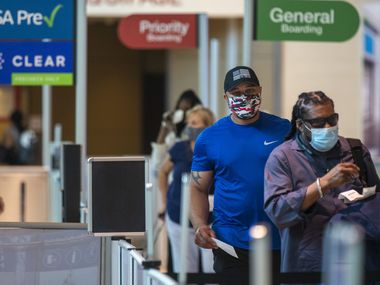 Masked passengers walk to the security checkpoint at Dallas Love Field airport in Dallas on a recent morning.