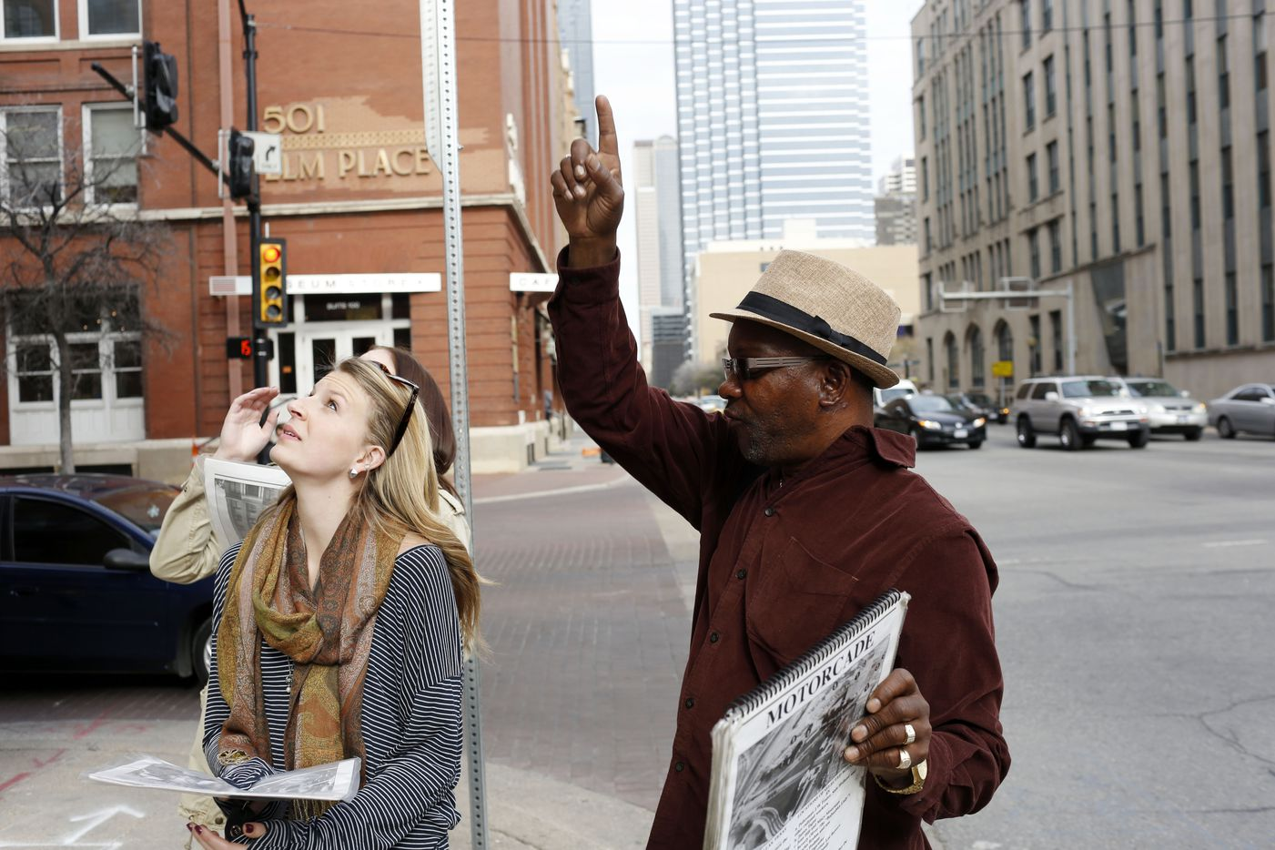Lacey Gardner (left) and Chelsey Healy (behind Gardner) listen as Ron Washington points to the window on the sixth floor of the former Texas School Book Depository building as he tells them about parts of his JFK conspiracy booklet he is trying to sell in Dealey Plaza in Downtown Dallas on March 6, 2013.
