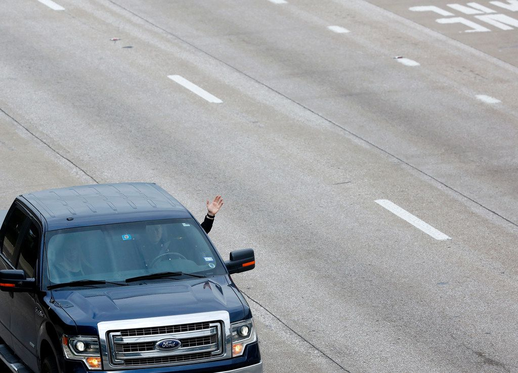 A member of the funeral procession for Dallas police Officer Rogelio Santander waves to Richardson firefighters and police officers gathered on North Central Expressway and Galatyn Parkway in Richardson, Texas on Tuesday, May 1, 2018. Santander was shot and killed last week while trying to arrest a man at a Home Depot.