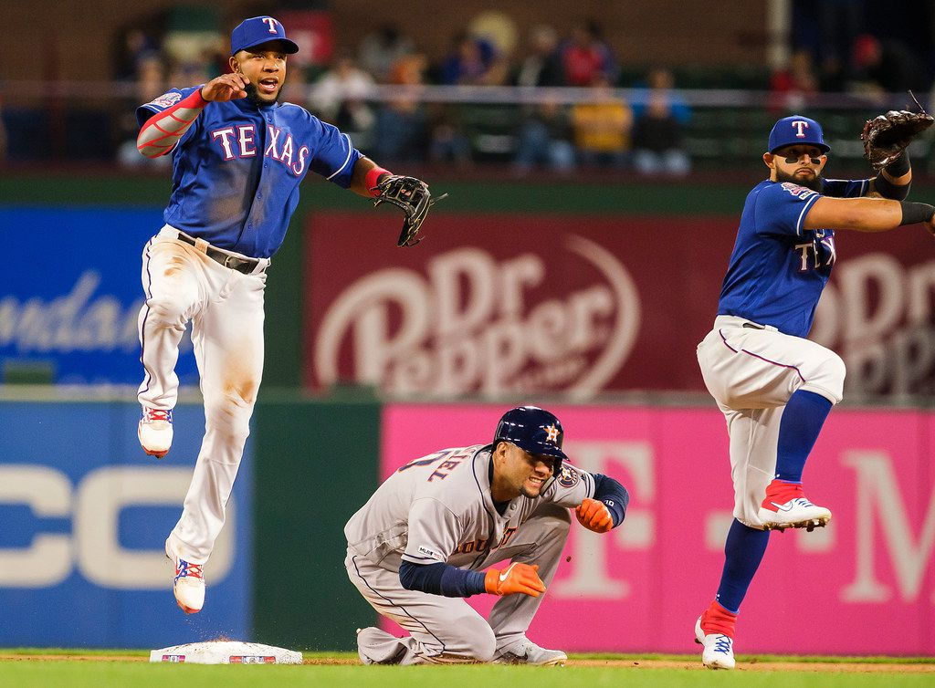 Texas Rangers shortstop Elvis Andrus (left) is mirrored by second baseman Rougned Odor as he completes the relay on a double play over Houston Astros first baseman Yuli Gurriel to get designated hitter Tyler White at first during the fourth inning at Globe Life Park on Wednesday, April 3, 2019, in Arlington. (Smiley N. Pool/The Dallas Morning News)