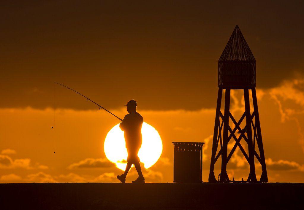 En esta imagen del 14 de julio de 2016, un pescador se prepara para lanzar su línea al amanecer en un muelle del Océano Atlántico en Bal Harbour, Florida. (AP Foto/Wilfredo Lee, Archivo)