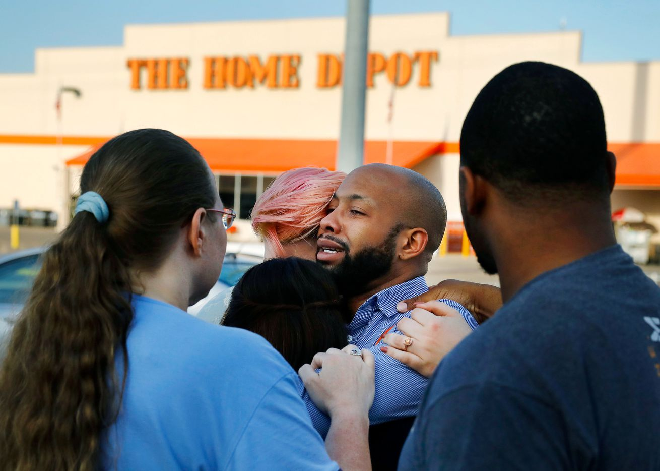 Home Depot employees comfort one another outside the store after two police officers and a civilian were shot by a man on April 24, 2018, in Dallas. The officers were critically wounded in the shooting, according to officials.