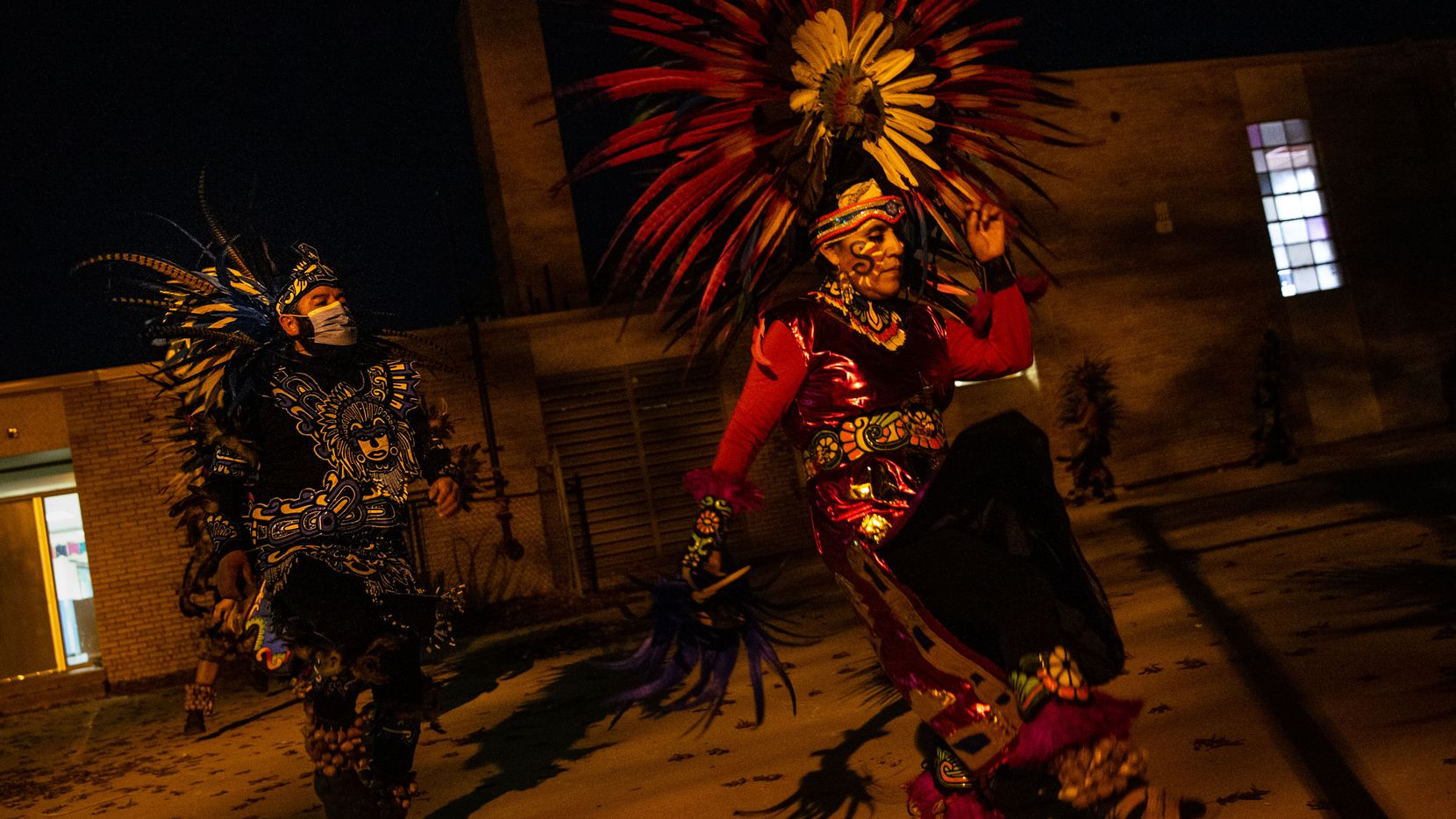 Gloria Flores (right) and other members of Danza Chichimeca San Miguel de Arcángel run through dress rehearsal for celebrations of Day of the Virgin of Guadalupe ceremonies, which are Saturday. The group practiced outside Stemmons Elementary School in west Oak Cliff. Outdoor rehearsals are among several steps that matachines dance groups have taken this year to keep people safe during the pandemic.