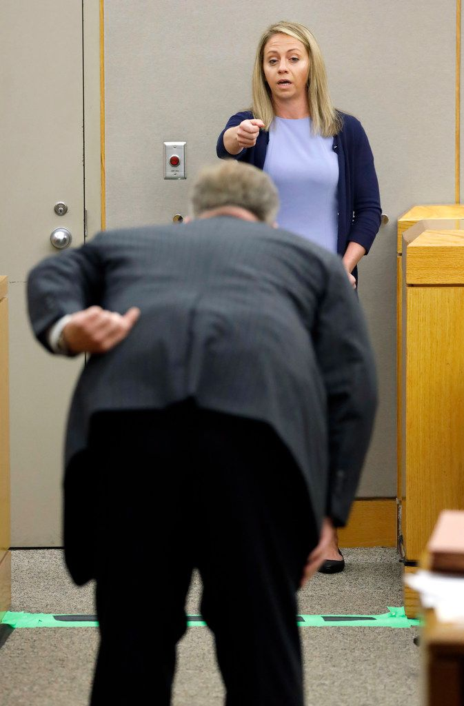 Prosecutor Jason Hermus (back to camera) asks Amber Guyger to pretend to aim a gun at him like she did the night of the shooting. (Tom Fox/Staff Photographer)