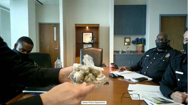Dallas Police Chief Eddie Garcia holds up a bag of marijuana during his first public safety committee meeting as chief, which was held virtually, in Dallas on Monday, Feb. 8, 2021.