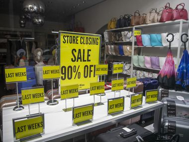 """Store Closing"" sale signs on display at a shop on Madison Avenue in New York."