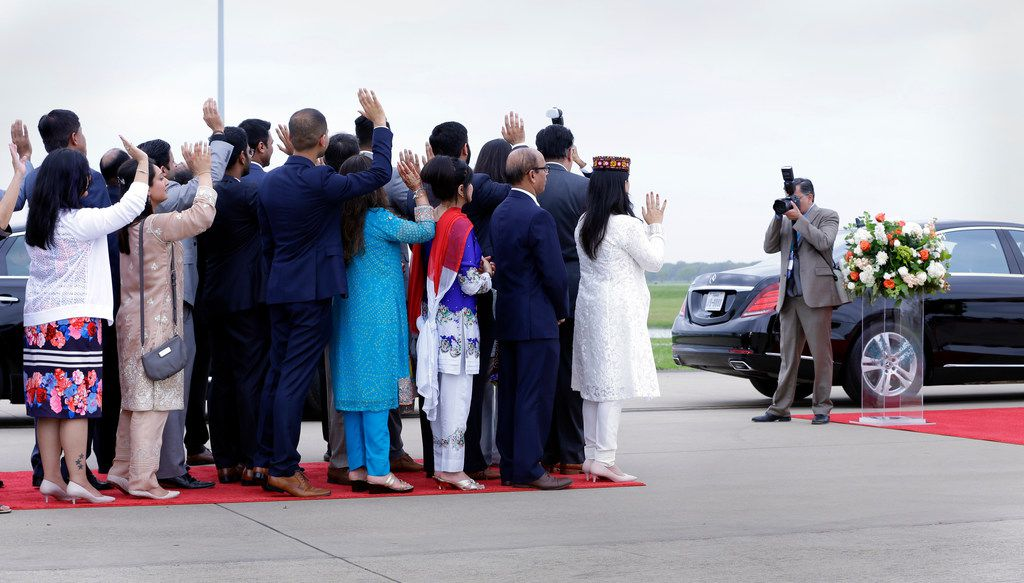 Attendants wave as the Aga Khan leaves in his motorcade at the Sugar Land Regional Airport.