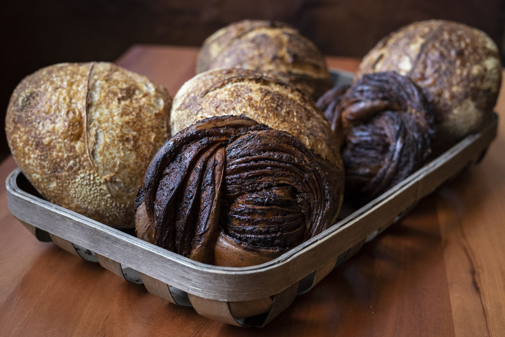 A basket of Chocolate Babka bread, bottom-center, and Sourdough Blue Tinge Emmer, from Lucia restaurant in Dallas