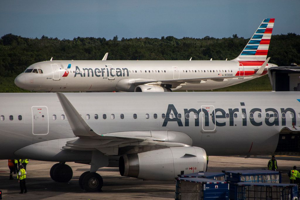 An American Airlines plane taxis away from another parked at the gates of Las Americas International Airport in Santo Domingo, Dominican Repbulic.  (Smiley N. Pool/The Dallas Morning News)
