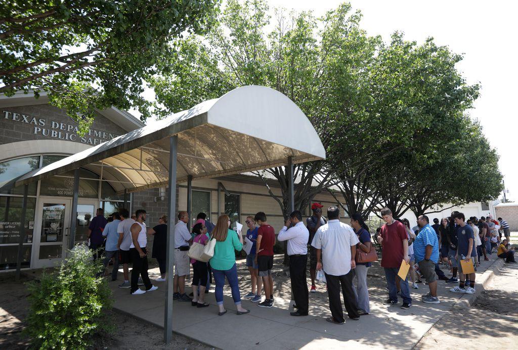 Decenas de personas hacen fila en las afueras de un centro de procesamiento de licencias en McKinney, en pleno calor del verano.